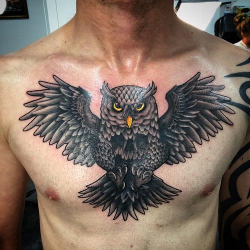 Blackwork uil tattoo met kleurelementen op de borst