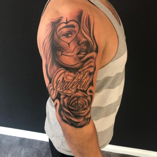 Chicano tattoo met freehand lettering en roos