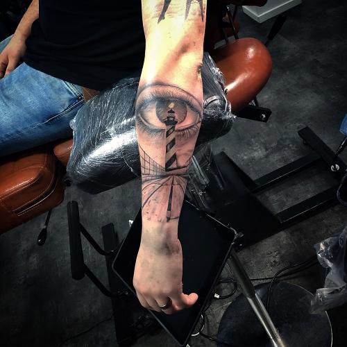 Custom tattoo design van een vuurtoren met realistisch oog