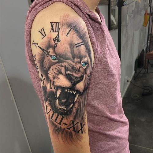 Klok met leeuw kleurogen realistisch tattoo bovenarm
