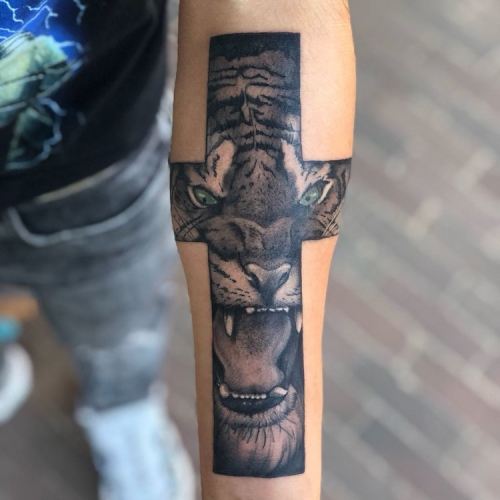 Tattoo van kruis leeuw kleur ogen onderarm