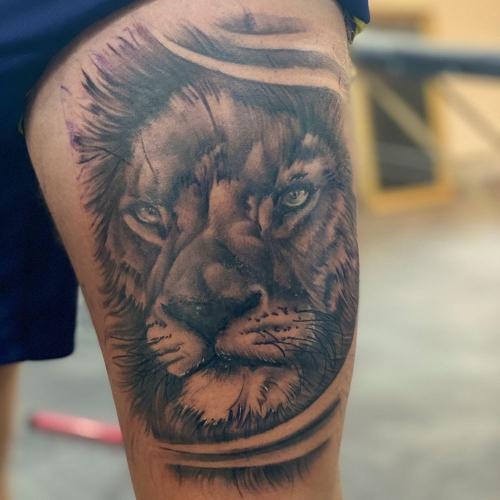 Realistische tattoo van leeuw op het bovenbeen