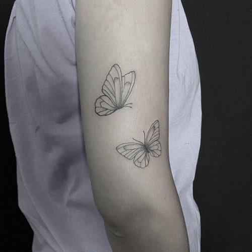 Fijn lijnwerk minimalistische vlinder tattoo