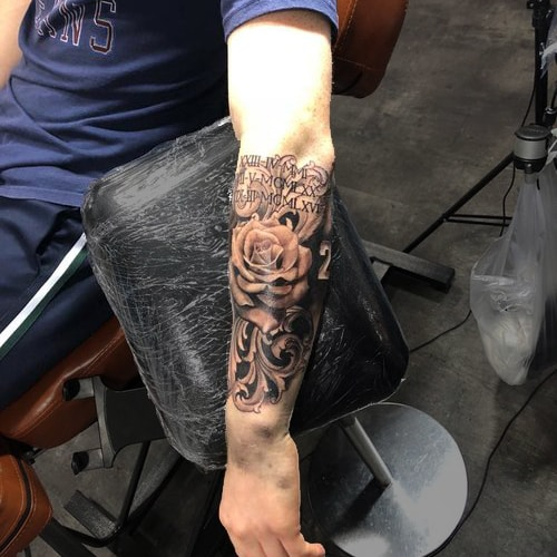 Begin van een realistische tattoo sleeve met roos en Romeinse cijfers