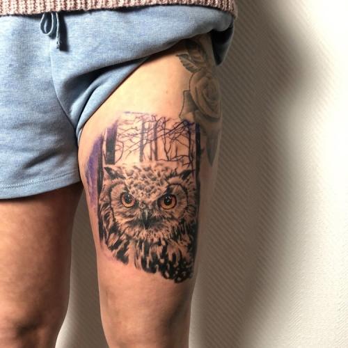 Realistische uil met kleurogen op het bovenbeen tattoo