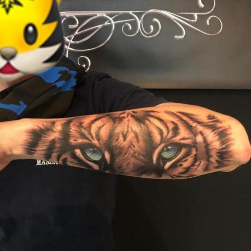 Tijger tattoo met kleurogen op de onderarm