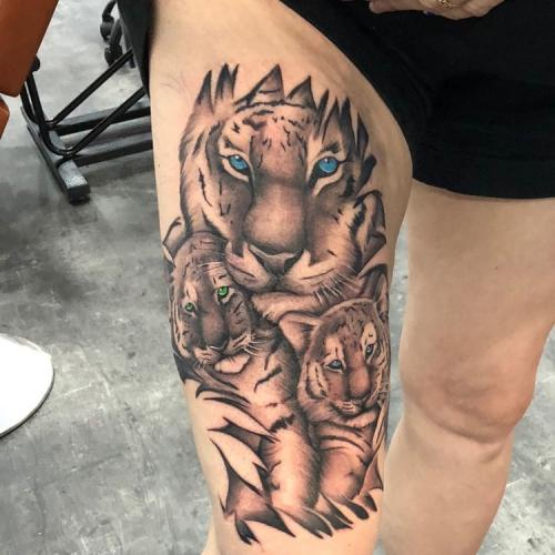 Tijgerfamilie tattoo op bovenbeen met kleurogen