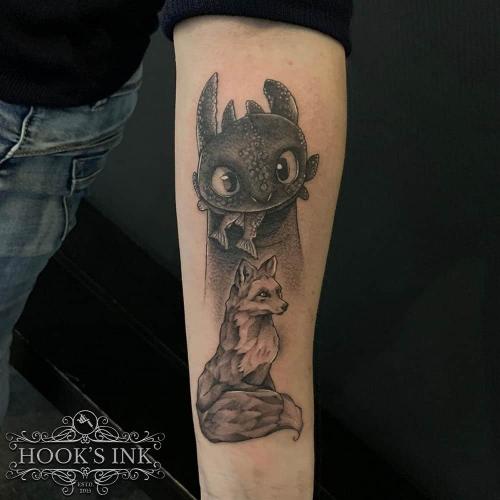 Custom made tattoo met Toothless uit How to train your dragon en een vosje