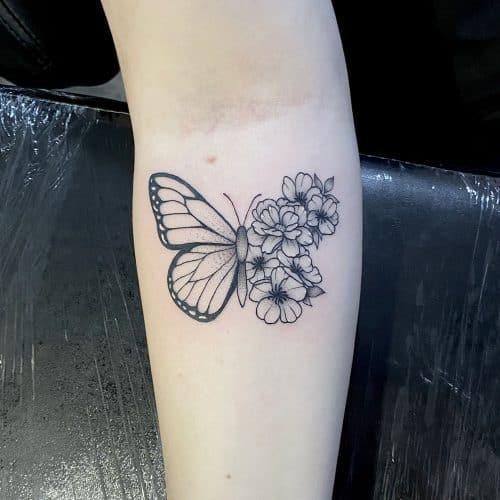 Vlinder met bloemen witte accenten tattoo Danique