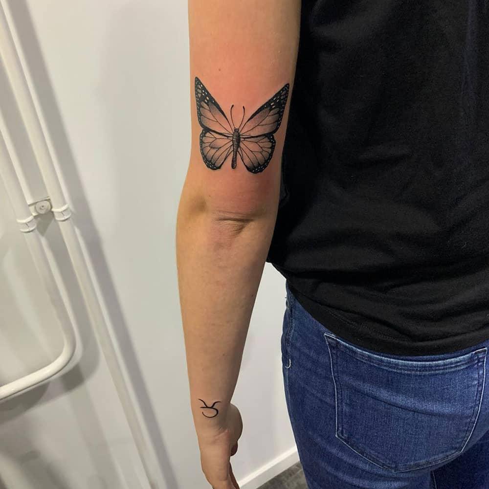 Black & grey vlinder boven elleboog kleine tattoo op de pols