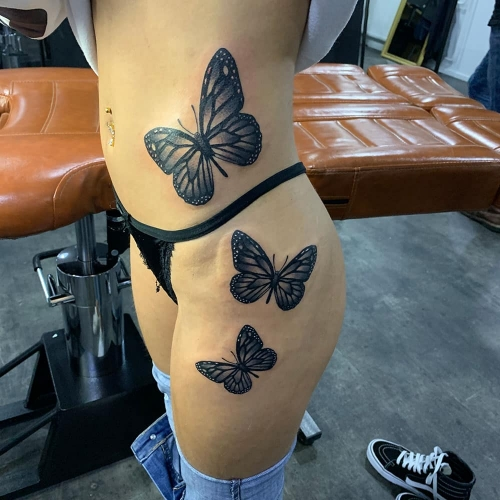 Drie vlinders tattoo zijkant lichaam en dijbeen