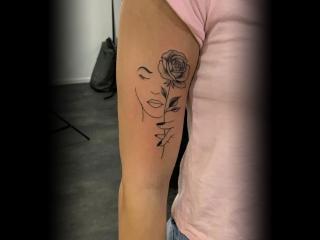 Fineline tattoo van roos en gezicht